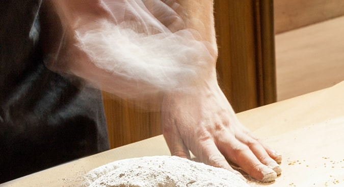 Hands kneading dough to make our PITTABUNS bread